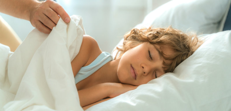 Enfants qui dort paisible et un adulte remet sa couverture pour empêcher l'hypersomnie